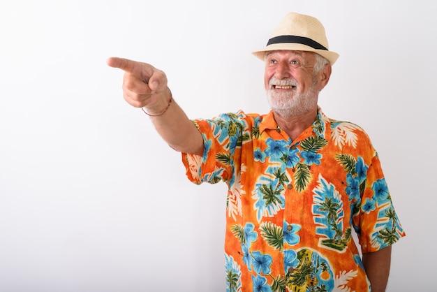 Szczęśliwy starszy mężczyzna brodaty turysta uśmiecha się wskazując na odległość podczas noszenia kapelusza na białym tle