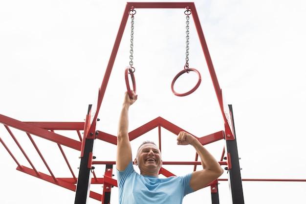 Szczęśliwy starszy mężczyzna ćwiczy na świeżym powietrzu