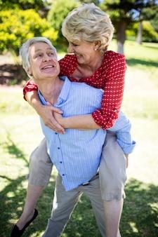 Szczęśliwy starszy mężczyzna daje piggyback starszej kobiecie