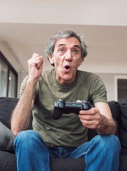 Szczęśliwy starszy mężczyzna gra wideo
