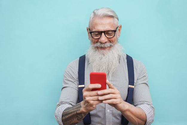 Szczęśliwy starszy mężczyzna hipster za pomocą telefonu komórkowego na zewnątrz w mieście