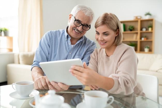 Szczęśliwy starszy mężczyzna i jego córka patrząc na ekran touchpada, rozmawiając z kimś przez czat wideo