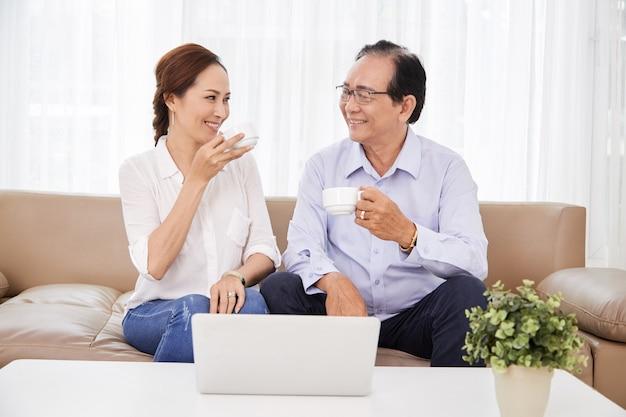 Szczęśliwy starszy mężczyzna i kobieta piją kawę i patrzą na siebie, siedząc na kanapie z otwartym laptopem