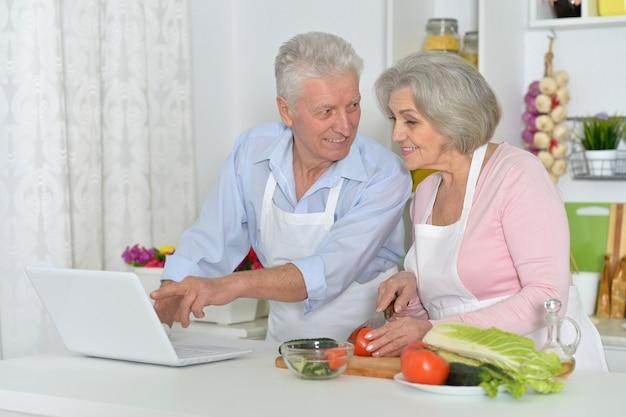 Szczęśliwy starszy mężczyzna i kobieta w kuchni z laptopem
