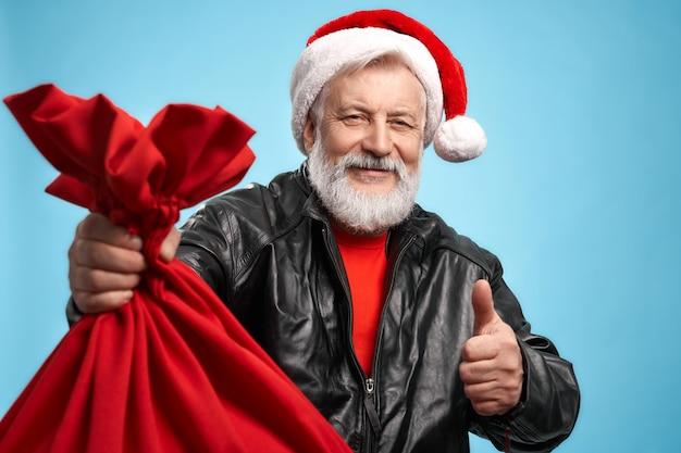 Szczęśliwy starszy mężczyzna jest ubranym boże narodzenie kapelusz i czarną kurtkę