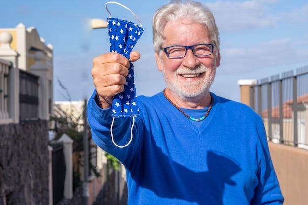 Szczęśliwy starszy mężczyzna już zaszczepiony przeciwko zakażeniu koronawirusem uśmiechający się na zewnątrz, biorąc do ręki maskę ochronną. nieostre ludzie