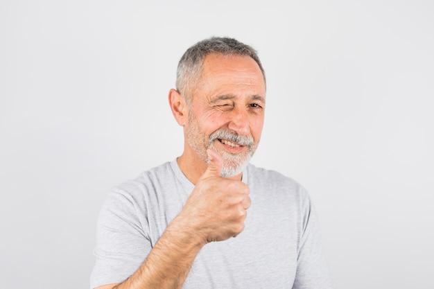 Szczęśliwy starszy mężczyzna mruga i pokazuje jak