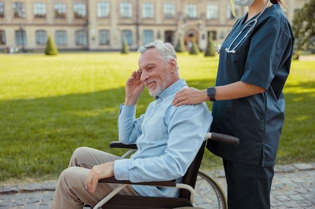 Szczęśliwy starszy mężczyzna odzyskujący pacjenta na wózku inwalidzkim na spacerze z pielęgniarką noszącą osłonę twarzy i