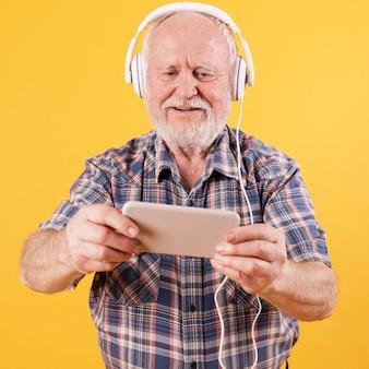 Szczęśliwy starszy mężczyzna ogląda wideo muzykę