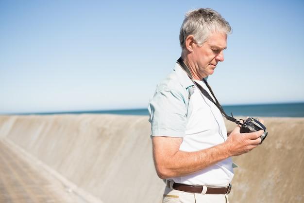 Szczęśliwy starszy mężczyzna patrzeje jego kamerę