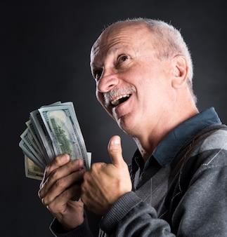 Szczęśliwy starszy mężczyzna pokazujący dolary na ciemnym tle