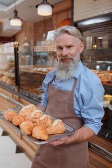 Szczęśliwy starszy mężczyzna pracujący w swoim sklepie piekarniczym, niosąc tacę z rogalikami