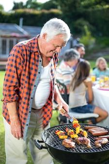 Szczęśliwy starszy mężczyzna przygotowywa jedzenie na grillu