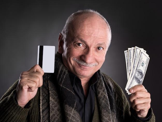 Szczęśliwy starszy mężczyzna trzymający banknoty dolarowe i kartę kredytową na ciemnym tle