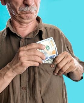 Szczęśliwy starszy mężczyzna trzymający banknoty dolarowe na niebieskim tle