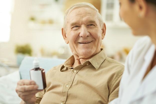 Szczęśliwy starszy mężczyzna trzymający lek w domu