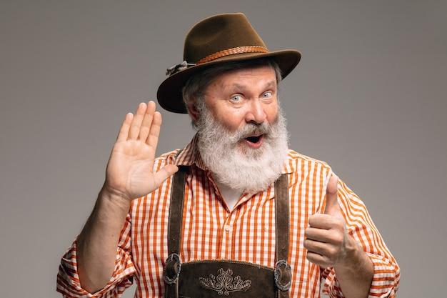 Szczęśliwy starszy mężczyzna ubrany w tradycyjny austriacki lub bawarski strój, gestykulując na białym tle