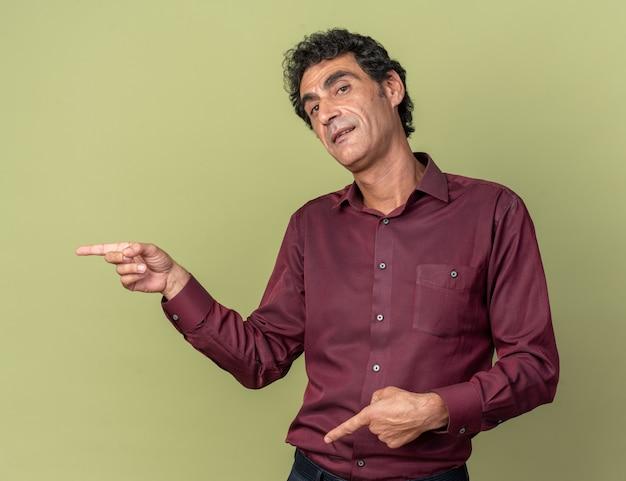 Szczęśliwy starszy mężczyzna w fioletowej koszuli patrzący na aparat uśmiechający się wskazujący palcami wskazującymi w bok, stojący nad zielenią