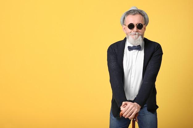 Szczęśliwy starszy mężczyzna w hipsterskim stroju na żółto