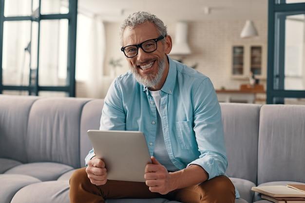 Szczęśliwy starszy mężczyzna za pomocą cyfrowego tabletu i patrząc na kamerę siedząc na kanapie w domu
