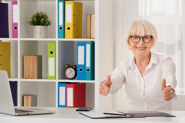 Szczęśliwy starszy obsiadanie na jej biurze