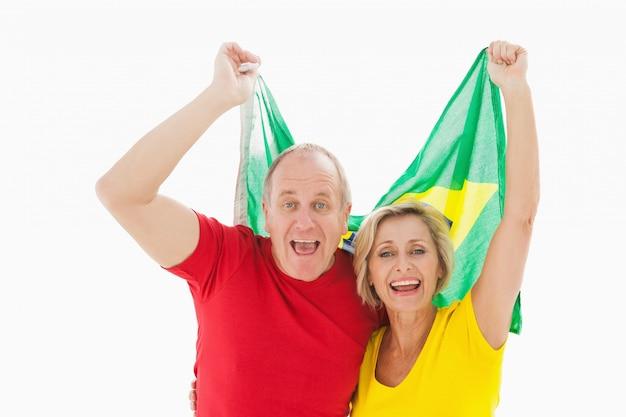 Szczęśliwy starszy para doping przy kamerą trzyma brazil flaga