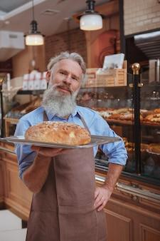Szczęśliwy starszy piekarz trzymający świeżo upieczony chleb na tacy uśmiechając się dumnie do kamery