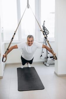 Szczęśliwy starszy sportowiec ćwiczy z trx