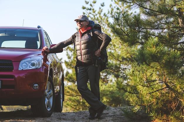 Szczęśliwy starszy turysta z plecakiem oparty na czerwonym samochodzie w lesie