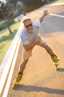 Szczęśliwy staruszek w okularach przeciwsłonecznych jeżdżący na rolkach po alejce