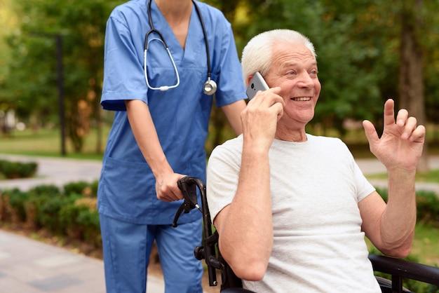 Szczęśliwy stary człowiek na wózku inwalidzkim rozmawia przez telefon komórkowy