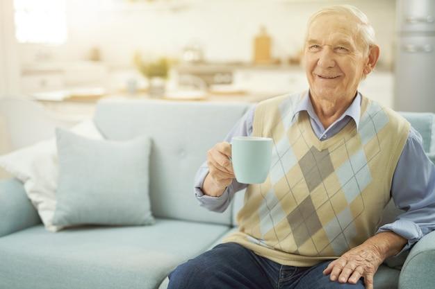 Szczęśliwy stary człowiek odpoczywający na kanapie z filiżanką herbaty