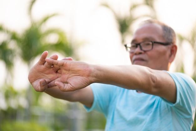 Szczęśliwy stary człowiek rozciąganie ręki przed ćwiczeniami na świeżym powietrzu w parku