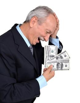 Szczęśliwy stary człowiek trzymający banknoty dolarowe