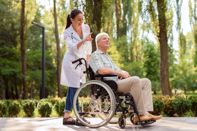 Szczęśliwy stary człowiek w wózku inwalidzkim w parku z lekarką