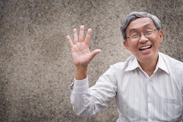 Szczęśliwy stary człowiek wskazując pięć palców