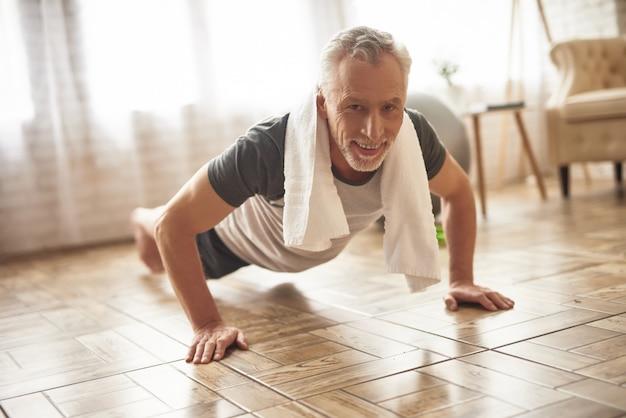 Szczęśliwy stary sportowiec robi deski opieki zdrowotnej.