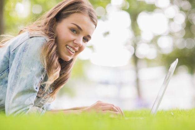Szczęśliwy studencki lying on the beach na trawie używać jej laptop patrzeje kamerę