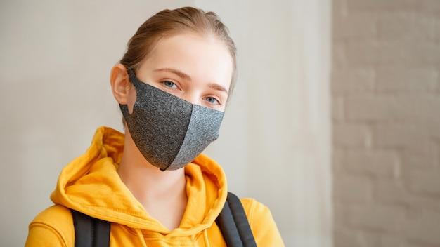 Szczęśliwy student na ścianie z cegły młoda piękna kobieta uśmiecha się szczerze nosząc maskę ochronną portret z plecakiem nastoletnia dziewczyna blondynka kaukaski nastolatek podróżnik w masce długi baner internetowy kopia przestrzeń