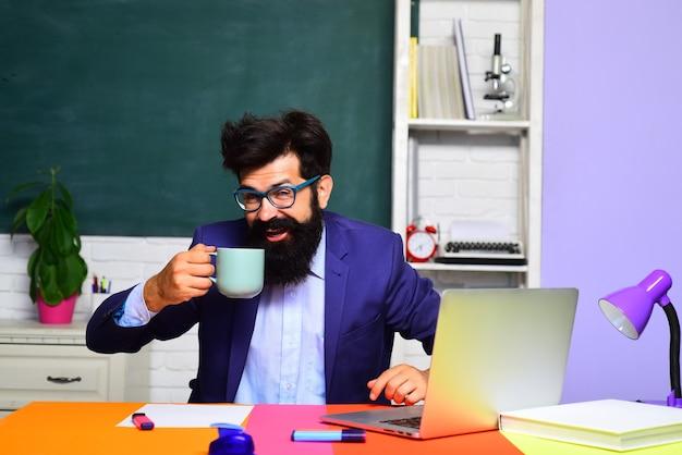 Szczęśliwy student pije kawę z powrotem do szkoły młody szczęśliwy brodaty nauczyciel student na uniwersytecie