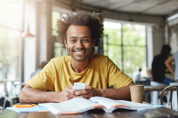 Szczęśliwy studentka na sobie żółtą koszulkę siedzi w kawiarni