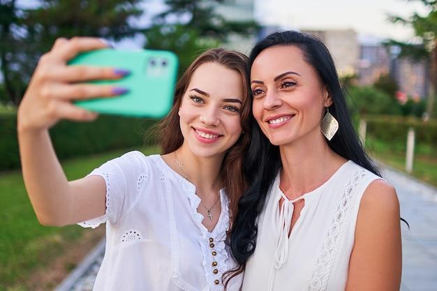Szczęśliwy stylowy atrakcyjny uśmiechnięta córka z matką wziąć selfie zdjęcie portret na aparat w telefonie podczas spaceru razem na zewnątrz