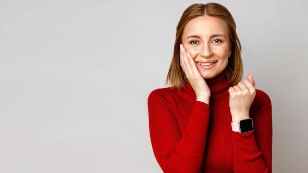 Szczęśliwy stylowy biznes kobieta w czerwonym golfie pokazuje smartwatch na nadgarstku, śmiejąc się i dotykając jej twarzy ręką, patrzy na ciebie. na białym tle na szarej powierzchni