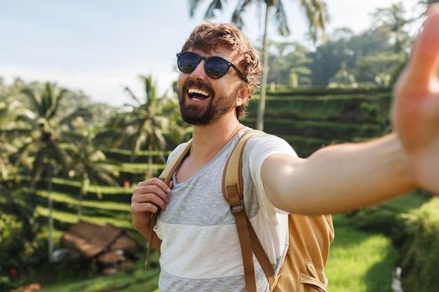 Szczęśliwy stylowy kaukaski mężczyzna z plecakiem podróżuje na plantacji ryżu i robi autoportrety na wspomnienia.