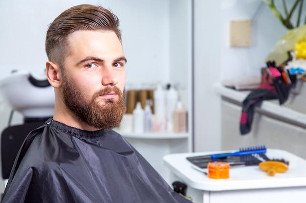 Szczęśliwy stylowy mężczyzna w salonie fryzjerskim, patrząc na kamery po pracy.