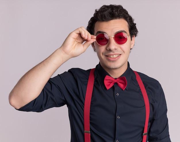 Szczęśliwy stylowy mężczyzna z muszką w okularach i szelkach patrząc z przodu z uśmiechem na twarzy stojącej na białej ścianie