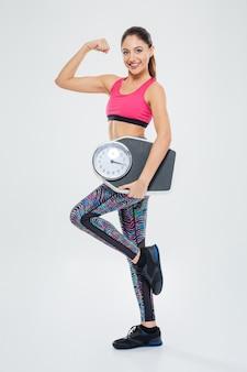 Szczęśliwy sukces fitness kobieta trzyma maszynę do ważenia