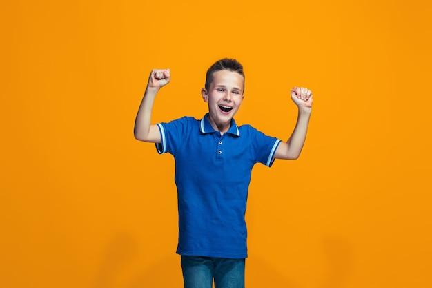 Szczęśliwy sukces nastolatek chłopiec świętuje bycie zwycięzcą.