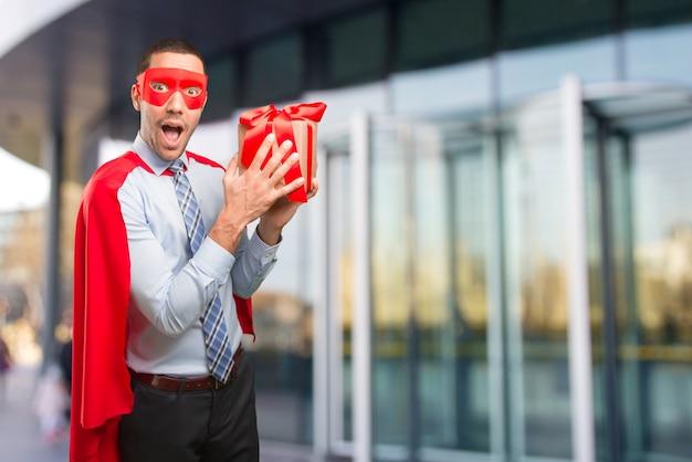Szczęśliwy super biznesmen z prezentem
