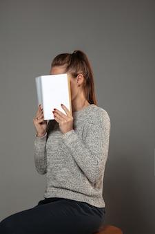 Szczęśliwy światowy dzień książki i praw autorskich, przeczytaj, aby stać się kimś innym - kobietą zakrywającą twarz książką podczas czytania na szarej ścianie.